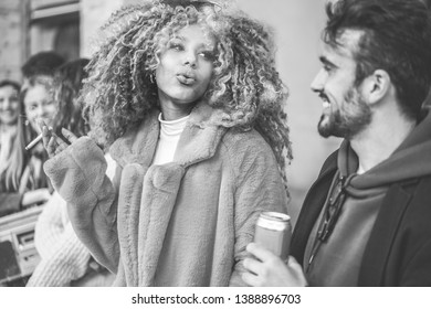 Trendy people from diverse culture making party outdoor drinking beer, smoking and listening music - Young friends having fun on weekend evening day - City life concept - Focus on afro girl face