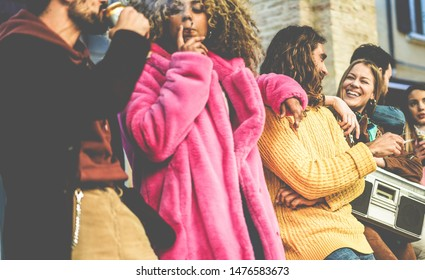 Trendy people from diverse culture making party outdoor drinking beer, smoking and listening music - Young friends having fun on weekend evening day - City life concept - Focus on man with long hair