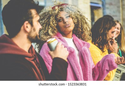 Trendy people from diverse culture making party outdoor drinking beer, smoking and listening music - Young friends having fun together - Festival and weekend  concept - Focus on afro girl face