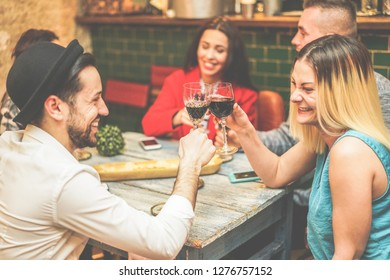 Trendy people drinking red wine in a fashion winery bar shop - Young happy friends cheering at appetizer party dinner - Youth and friendship concept - Focus on glasses