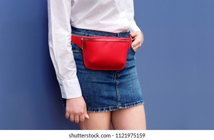 Trendy red stylish belt leather bag clutch on young woman