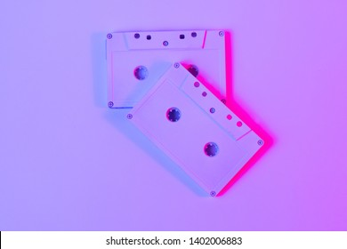 Trendy reviving retro audio cassette tape on pink and green neon light. Analogue music hipster trend. Bright neon colors. Minimal and surreal. style of the 80's Top view