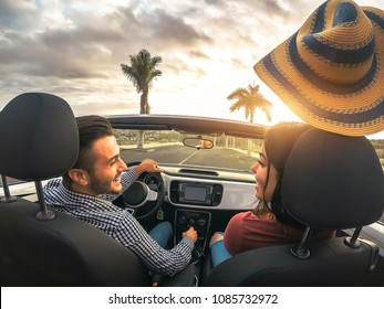 Trendy rich couple having fun driving convertible car at sunset - Happy romantic lovers enjoying their road trip in cabriolet auto - Love, relationship and youth romance holidays lifestyle