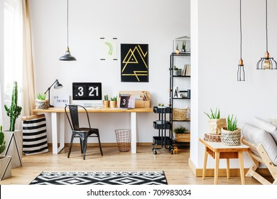Trendy room with workspace for a freelancer with white wall, desk, black vintage chair, industrial lamps, poster and wooden sofa in bright open living room