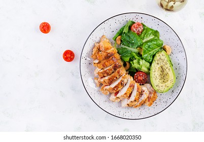 Trendy salad. Chicken grilled fillet with salad fresh tomatoes and avocado. Healthy food, ketogenic diet, diet lunch concept. Keto/Paleo diet menu. Top view, overhead, flat lay