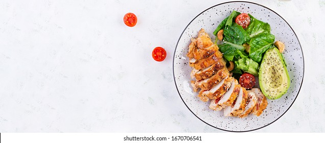 Trendy salad. Chicken grilled fillet with salad fresh tomatoes and avocado. Healthy food, ketogenic diet, diet lunch concept. Keto/Paleo diet menu. Top view, overhead, banner