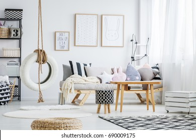 Trendy scandi white room with simple tire swing