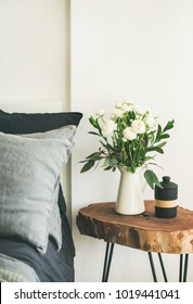 Trendy Scandinavian style interior shot. Bedroom with washed linen grey pillows and rough wooden nightstand with bucket of flowers and candle, copy space. Minimalistic, eco design
