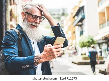 Trendy senior man using smartphone app in downtown center outdoor - Mature fashion male having fun with new trends technology - Tech and joyful elderly lifestyle concept - Focus on his face