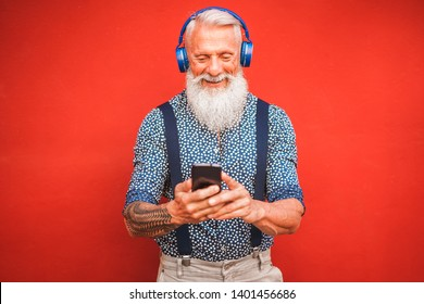 Trendy senior man using smartphone app with red backgorund - Mature fashion male having fun with new trends technology - Tech and joyful elderly lifestyle concept - Focus on his face
