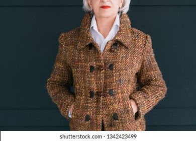 Trendy senior wardrobe. Female style and elegance. Aged lady posing in fashion tweed autumn outfit with hands in pockets.