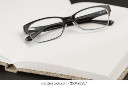 Trendy silver and black glasses on open book with blank pages. Close up with selective focus and blur.