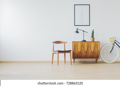 Trendy spacious room with antique wooden furniture, white wall, cupboard, chair and vintage bike