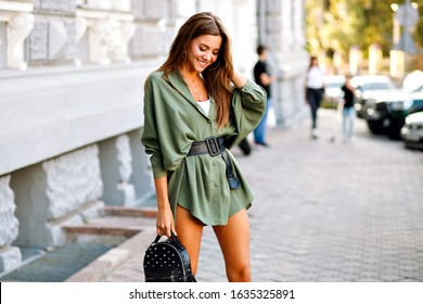 Trendy street style image of amazing fashionable young pretty woman posing on the street, wearing mini shirt dress and small backpack, warm colors, horizontal, sunny summer time.