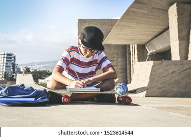Trendy student doing homework out of the college sitting on a concrete wall. Young boy writing on an exercise book using a skateboard like a desk in a urban context. Educational school,  youth concept