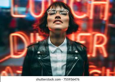 Trendy and stylis young woman in eyeglasses closed eyes enjoying in big city atmosphere in nigh, cool dressed hipster girl in spectacles with illumination reflection standing against nightlights