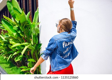 Trendy summer fashionable picture of woman posing back and dancing, stylish denim jacket and dress, luxury hotel, free spirit mood.