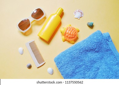 Trendy sunglasses, wooden comb, yellow sunscreen bottle, rubber toy turtle, blue towel and seashells. Flat lay summer holiday photo. Top view beach essentials