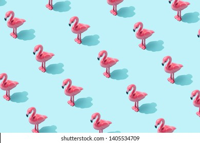 Trendy sunlight Summer pattern made with pink flamingo toy on bright light blue background. Minimal summer concept.