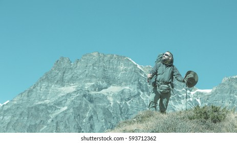 Trendy toned Portrait of bearded Hiker staying on rocky Slope in high Mountains with copy Space