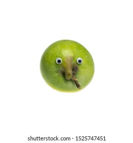 Trendy ugly food concept. Green funny apple with eyes isolated on white background. Fruit with a strange shape. The problem of food waste.