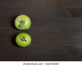 Trendy ugly food concept. Two green apples on a dark brown wooden background. Copy space. Fruit with a strange shape.