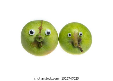 Trendy ugly food concept. Two green funny apples with eyes isolated on white background. Fruit with a strange shape. The problem of food waste.