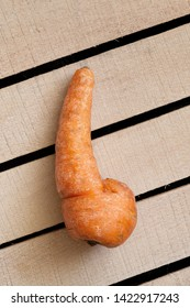 Trendy ugly organic carrot on wooden box background. Ugly food, unusual deformed fruits and vegetables, misshapen produce, zero waste concept. Top view, copy space, vertical