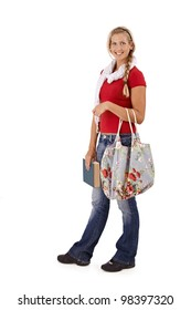 Trendy university student girl holding book and fashionable bag, smiling at camera, full length portrait.