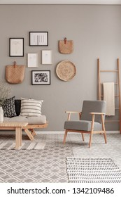 Trendy vintage armchair next to chic scandinavian sofa with pillows in classy living room interior