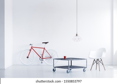Trendy white chair next to industrial do it yourself coffee table in bright interior with red bike