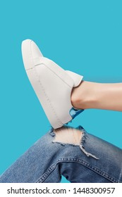 Trendy white eco leather sheakers on bent leg knee in ragged jeans over pastel turquoise blue background. Colorful main trend backdrop for your magazine, online store and media. Copy space