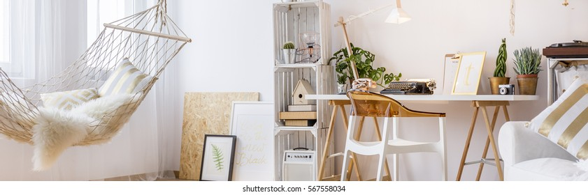 Trendy white room with hammock, pallet furniture, chair and desk
