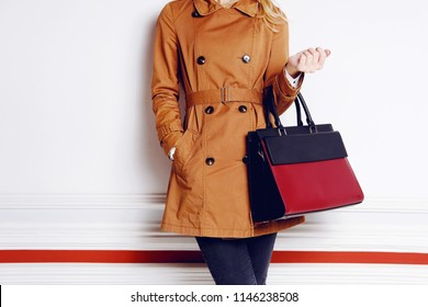 Trendy woman with black and red leather bag in hand. Fashion autumn outfit coat
