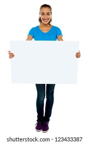 Trendy woman displaying blank billboard. Full portrait