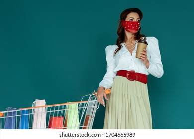 trendy woman in red mask holding coffee to go and standing near shopping cart with shopping bags isolated on blue