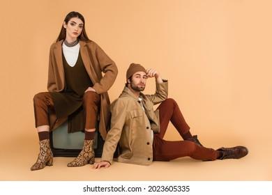 trendy woman sitting on vintage tv set near stylish man on floor on beige background