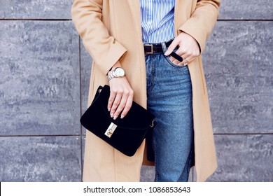 Trendy woman in stylish beige coat and jeans with little black bag clutch . Fashion accessories
