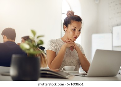 Trendy woman watching an online masterclass on a laptop in headphones in coworking space waiting for a client meeting