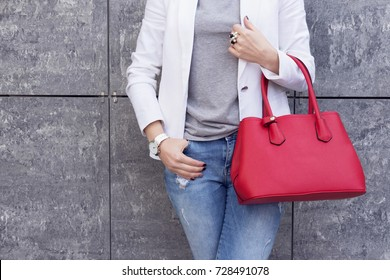 Trendy woman in white jacket with red bag in hand street look. Casual classic outfit