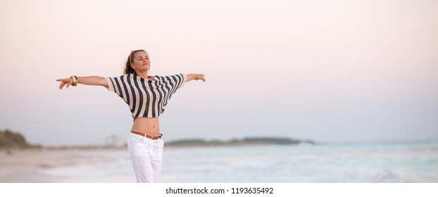 trendy woman in white pants and striped shirt on the seacoast in the evening rejoicing