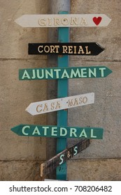 Trendy wooden signpost directing to places in Girona showing to the Cathedral, Casa Masó and the Adjuntament
