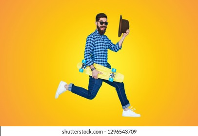 Trendy young bearded man jumping with yellow skateboard against the colorful yellow wall.