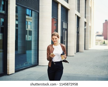 Trendy young blond woman in jacket having coffee and surfing phone while walking on street