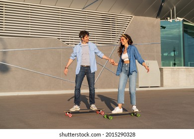 Trendy young couple riding longboards together holding hands. Stylish caucasian man and woman wearing street fashion clothes longboarding in summer city urban space. Happy casual friends on skateboard