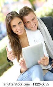 Trendy young couple in town using tablet