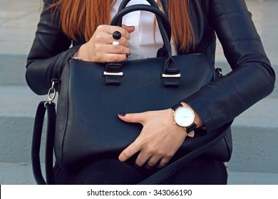 Trendy young girl in black leather jacket holding big black handbag street background .  Fashion accessories
