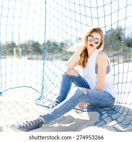 Trendy young girl posing against a background of blue football goal on a beach in the summer at the sea in sunglasses.