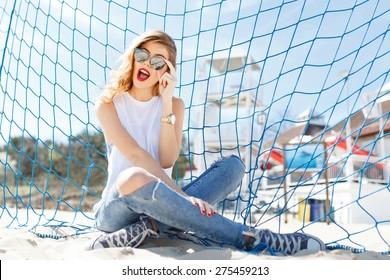 Trendy jung Mädchen posiert auf einem Hintergrund von blauem Fußball Tor auf einem Strand im Sommer auf dem Meer in Sonnenbrille.
