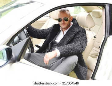 Trendy young guy in autumn clothes in sunglasses inside a sportive white car. Elegant business man posing at the wheel of his new sports car